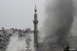 Smoke rises from a mosque and another building during heavy fighting between the Free Syrian Army and President Bashar al-Assad's forces, in the Jobar area of Damascus Feb. 6, 2013.