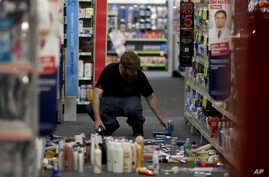 A man picks up fallen goods at a CVS store after an earthquake, March 28, 2014, in La Mirada, California.