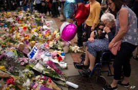 Women cry after placing flowers in a square in central Manchester, Britain, May 24, 2017, after the suicide attack at an Ariana Grande concert that left more than 20 people dead.