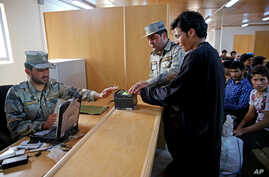 In this Monday, April 13, 2015 photo, Afghan border police officers help a returnee get his fingerprints scanned, at the Afghanistan-Iranian border point on the outskirts of Islam Qala in Herat province, west of Kabul, Afghanistan.