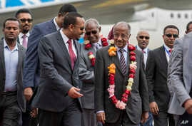 Eritrea's Foreign Minister Osman Sale, center right, is welcomed by Ethiopia's Prime Minister Abiy Ahmed, center left, upon the Eritrean delegation's arrival at the airport in Addis Ababa, Ethiopia, June 26, 2018.