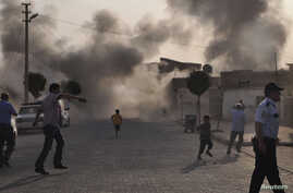 Smoke rises over the streets after an mortar bomb landed from Syria in the border village of Akcakale, southeastern Sanliurfa province, October 3, 2012.