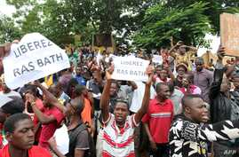 """People hold placards reading """"Free Rasbath,"""" a young radio presenter Mohamed Youssouf Bathily also known as """"Rasbath"""" who was arrested two days ago, as they take part in a demonstration in front of Bamako's court in Mali, Aug. 17, 2016."""