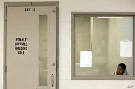 FILE - A juvenile detainee sits in a holding cell at a U.S. Customs and Border Protection processing facility in Brownsville, Texas, June 18, 2014.