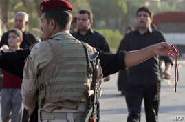 An Iraqi soldier mans a checkpoint on a road in Baghdad's