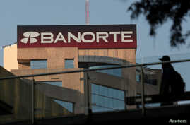FILE - A man walks past the headquarters of Banorte bank in Monterrey, Mexico, Dec. 5, 2017.