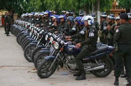 Cambodian military police officers stand by with their motorcycles at Stung Meanchey where Prime Minister Hun Sen made his first public appearance since Sunday's election, in Phnom Penh, July 31, 2013.