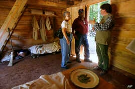 FILE - Ruth Toliner, left, and her husband Lowell Toliner, of Olney, Md., ask Steve Bashore questions about this newly reconstructed slave cabin at George Washington's Mount Vernon estate in Mt. Vernon, Va, Sept. 19, 2007.