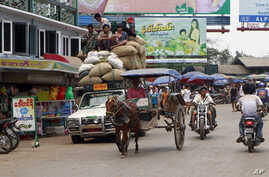 Vehicles make their way on a road near local bazaar in Mawlamyine, Mon State, Burma, March 11, 2011.