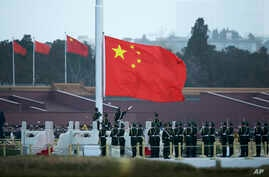 FILE - In this March 5, 2016, file photo, Chinese paramilitary policemen perform a flag raising ceremony on Tiananmen Square in Beijing.
