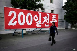 """A North Korean woman walks past a sign which reads """"200-day campaign,"""" in Pyongyang, North Korea on Saturday, June 25, 2016."""