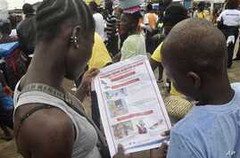 Liberian children read a leaflet with guidelines to protect the community from the Ebola virus,  in Monrovia, Liberia. Monday, Oct. 13, 2014. Some nurses in Liberia defied calls for a strike on Monday and turned up for work at hospitals amid the wors