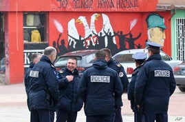 """Police officers stand by the graffiti that shows Serbian coat of arms and silhouettes of people, reading: """"... because there's no turning back,"""" in northern Serb-dominated part of ethnically divided town of Mitrovica, Kosovo, Nov. 23, 2018. Kosovo po"""