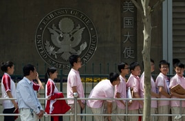 FILE -- In this May 2012 file photo, Chinese students wait outside the U.S. Embassy for their visa application interviews in Beijing, China.