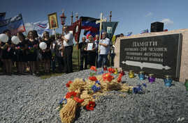 FILE- People stand with Orthodox crosses and icons as they attend a memorial service at the crash site of the Malaysia Airlines Flight 17, near the village of Hrabove, eastern Ukraine, July 17, 2015.