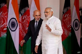 Indian Prime Minister Narendra Modi, foreground, and Afghan President Mohammad Ashraf Ghani walk for a meeting in New Delhi, India, Tuesday, April 28, 2015.