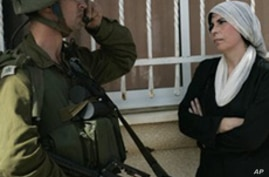 A Palestinian woman stands next to an Israeli soldier during a protest against the expansion of the nearby Jewish settlement of Halamish in the West Bank village of Nabi Saleh near Ramallah, Friday, Oct. 22, 2010.
