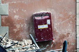 Rubble lies on the ground beside a postbox in the Piazza della Repubblica in Central L'aquila (January 2010 file photo)