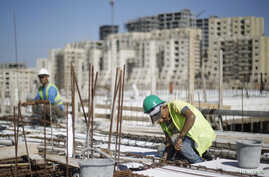 "FILE - Palestinian laborers work at a construction site in the new Palestinian town dubbed Rawabi or ""The Hills"", near the West Bank city of Ramallah, Oct. 27, 2013."