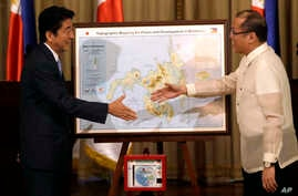 Japanese Prime Minister Shinzo Abe, left, and Philippine President Benigno Aquino III shake hands after Abe presented him with a topographical map of the country's third largest island of Mindanao at the conclusion of their joint press statement at M