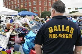 A Dallas firefighter pays respects at the makeshift memorial for fallen officers outside Dallas police headquarters in Texas, July 11, 2016. (M. O'Sullivan/VOA)
