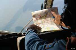 TOPSHOTSA Vietnamese Air Force crew member checks a map during a search flight some 200 km over the southern Vietnamese waters off Vietnam's island Phu Quoc on March 11, 2014.