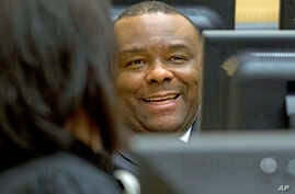 FILE  - Former Congo vice president Jean-Pierre Bemba smiles while waiting for the start of his trial, at the International Criminal Court in The Hague, Netherlands, Nov. 27, 2013.