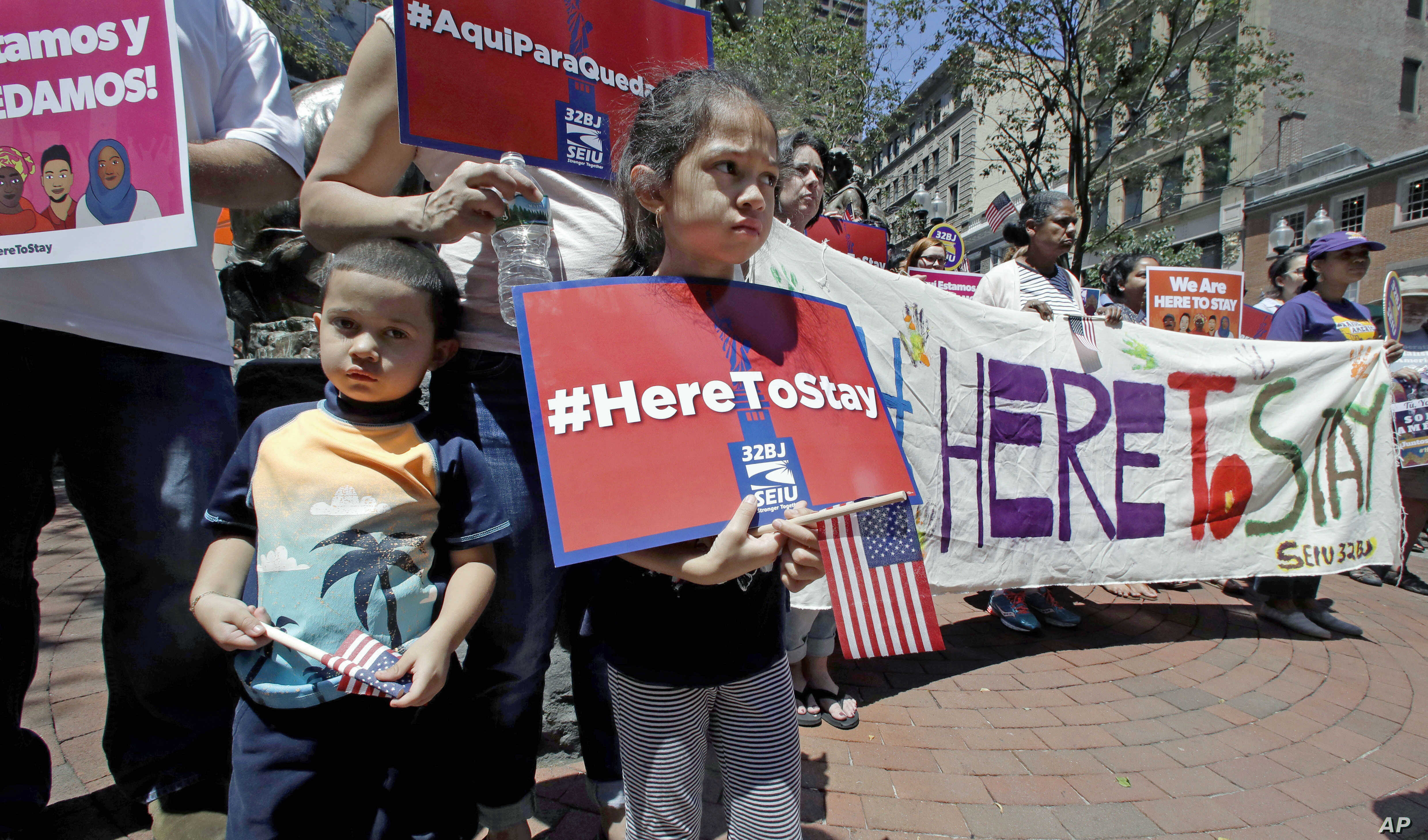"""Nicole Castillo, 7, of East Boston, holds a sign while standing with her brother Diego, 4, and mother Elsa, who is originally from El Salvador, during a """"Here to Stay"""" rally at the Irish Famine Memorial in Boston, July 6, 2017."""