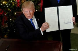 President Trump displays an executive order after he announced the U.S. would recognize Jerusalem as the capital of Israel, at the White House, Dec. 6, 2017.