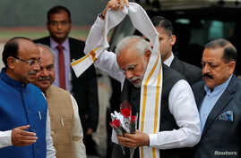India's Prime Minister Narendra Modi removes a stole given to him by a minister upon his arrival at the Parliament on the first day of the winter session in New Delhi, India, Dec. 11, 2018.