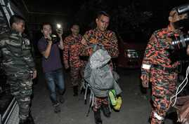 A member of a Malaysian rescue team, center, carries victims body parts inside a bag a day after the earthquake in Kundasang, a town in the district of Ranau, June 6, 2015.