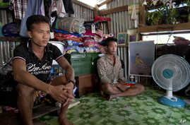 FILE - former Burmese slave fishermen Kaung Htet Wai, left, and Lin Lin sit in a small, wooden shack in Yangon, Myanmar. For the past .84 years, an exemption in U.S. law allowed the import of goods produced by slaves and others forced into labor
