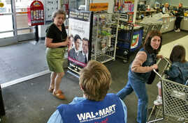 FILE - A store greeter offers help to shoppers at a Walmart store in West Norriton, Pa.