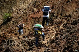 Residents carry food supplies along a landslide area near the site where dozens of victims are believed to have been buried in Itogon, Benguet province, northern Philippines, Sept. 19, 2018.