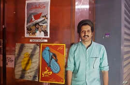 "In this Aug. 25, 2017 photo, Saudi filmmaker Ali Kalthami stands next to the poster for his film ""Wasati"" or ""Moderate"" and two other Saudi short films recently shown at Cinema Akil in Dubai, United Arab Emirates."