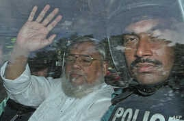 Secretary General of Jamaat-e-Islami, Ali Ahsan Mohammad Mujahid (L) waves from a police vehicle as he is transported to the central jail following his court verdict in Dhaka, Bangladesh, July 17, 2013.