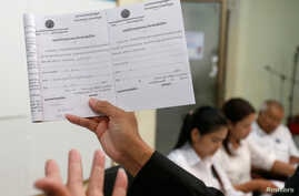 A member of the National Election Committee (NEC) and NEC's spokesman Dim Sovannarom shows a registration of political parties list to the media in Phnom Penh, Cambodia, April 30, 2018.