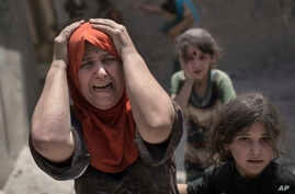 FILE - A woman screams while fleeing with her family through a destroyed alley, as Iraqi Special Forces continue their advance against Islamic State group militants, in the Old City of Mosul, Iraq, July 2, 2017.