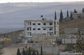 An Islamic State flag is seen atop a building in eastern Kobani, as seen from the Turkish border crossing of Mursitpinar as Kurdish Peshmerga forces fight against Islamic state fighters, Nov. 1, 2014.