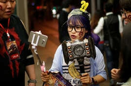 "A fan livestreams her participation during China's premiere of the film ""Warcraft"" at a theater in Shanghai, China, June 7, 2016."