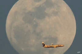 An Alaska Airlines flight passes by the rising moon Sunday, Feb. 21, 2016, in Phoenix.