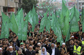 Palestinian Hamas supporters wave green Islamic flags as they chant Islamic slogans during a rally to commemorate the 27th anniversary of the Hamas militant group, at the main road in Jebaliya in the northern Gaza Strip, Friday, Dec. 12, 2014.