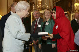 """Malala Yousafzai gives a copy of her book """"I am Malala"""", to Britain's Queen Elizabeth during a Reception for youth, education and the Commonwealth at Buckingham Palace in London October 18, 2013."""
