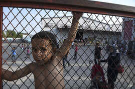 A child stands behind a fence during a protest against the living conditions at the Oreokastro camp, near the northern town of Thessaloniki, Greece, June 25, 2016.