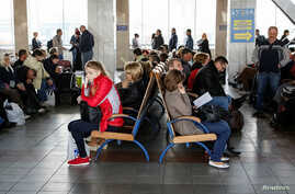 Passengers sit with their luggage while waiting for trains at the central railway station in Kyiv, Ukraine, April 19, 2016.