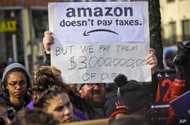 Protesters hold up anti-Amazon signs during a coalition rally and press conference of elected officials, community organizations and unions opposing Amazon headquarters getting subsidies to locate in Long Island City, Wednesday, Nov. 14, 2018, in New