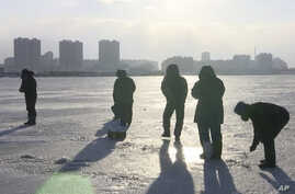 In this Jan. 18, 2016 image made from video, North Koreans stand on the frozen Taedong River as a man, right, ice fishes in Pyongyang, North Korea.