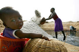 FILE - Mariama Diokh throws salt onto a pile while her 5-month-old infant sits in a nearby basket on the Senegalese coast close to the Gambian border in June 2006. A recent study done in Gambia found children conceived during lean times are susceptib