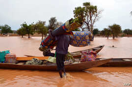 FILE - A man carries his belongings to a boat during flooding in a district in Niamey, Niger, Sept. 5, 2013.