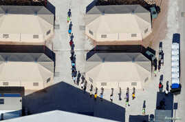 """Immigrant children, many of whom have been separated from their parents under a new """"zero tolerance"""" policy by the Trump administration, are shown walking in single file between tents in their compound next to the Mexican border in Tornillo, Texas, U"""